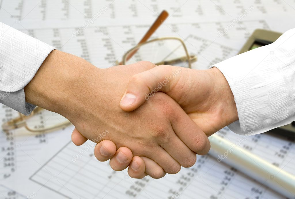 Handshake over paper and pen,blurry computer in the background — Stock Photo #1029474