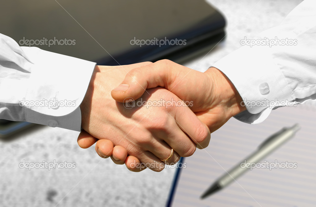 Handshake over paper and pen,blurry computer in the background — Stock Photo #1030348
