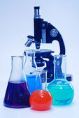 Laboratory glassware and microscope — Stock Photo