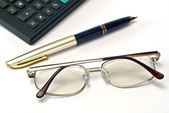 Calculator, pen and spectacles — Stock Photo