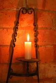 Candle in brass holder lighting wall of — Stock Photo