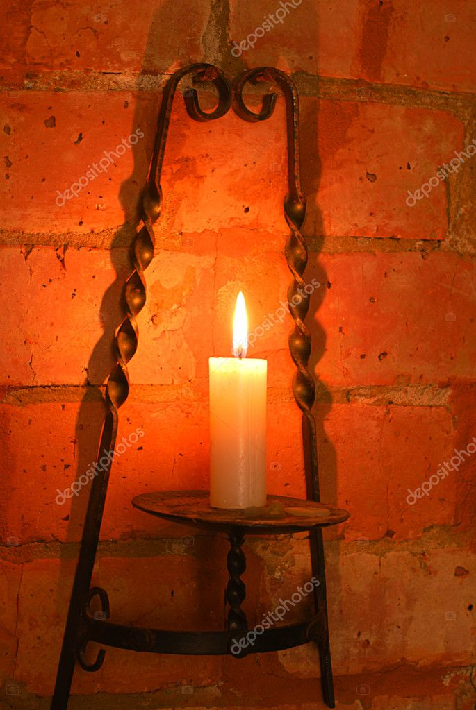 Candle in brass holder lighting wall of brick   Stock Photo #1013847
