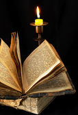 Old religious book and candle — Stock Photo