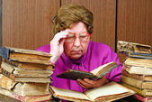 Old woman in library with religious — Stock Photo