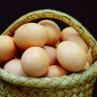 Eggs in a basket on a black background — Stock Photo