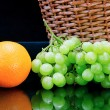 Fresh orange and grape near  basket - Stock Photo