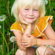 Little girl among dandelions — Stock Photo