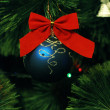 Blue ball with red bow on the tree — Stock Photo