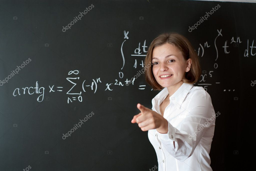 Young teacher is standing near blackboard in classroom  Stock Photo #1059647