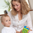 Stock Photo: Young mother plays with her son