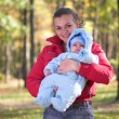 Mother with baby in autumn forest — Stock Photo
