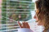 Ung kvinna väntar med hopp nära fönster — Stockfoto