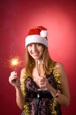 Smiling girl with Christmas sparkler — Stock Photo