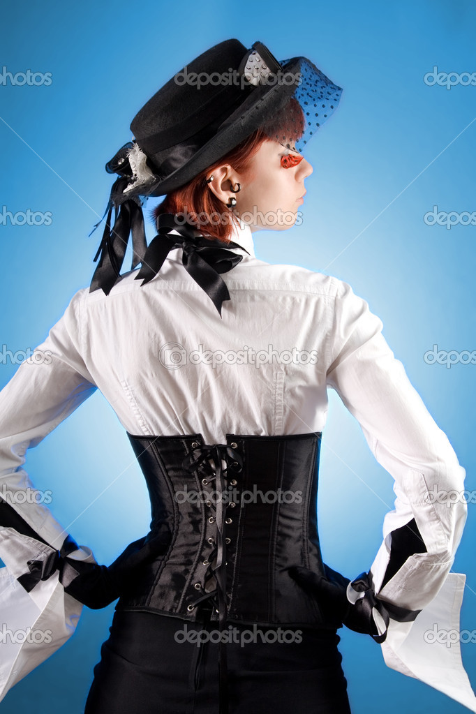Rear view of attractive girl in Victorian style clothes, studio shot over blue background   Stock Photo #1104565