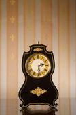 Vintage clocks on wallpaper background — Stock Photo