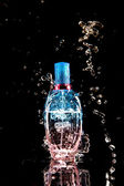 Perfume bottle with water splashes — Stock Photo