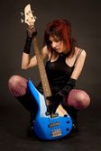 Attractive girl looking at bass guitar — Stock Photo