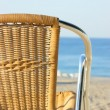 Wicker chair on the beach - Stock Photo