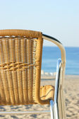 Wicker chair on the beach — Stok fotoğraf