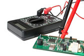 Electronic boards and digital multimeter — Stock Photo