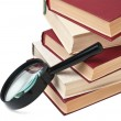 Stock Photo: Stack of books and magnifying glass