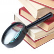 Stack of books and magnifying glass — Stock Photo #2333668