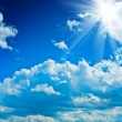 Beautyful cloudy blue sky with sun - Stock Photo