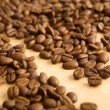 Coffee grains on paper — Stock Photo
