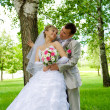 The groom and the bride near a tree — Stock Photo