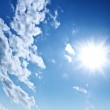 Blue cloudy sky and sun — Stock Photo