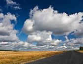 Road on the autumn field with cloudy sky — Stock Photo