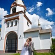 Newly married kiss on the church — Stock Photo