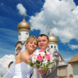 Newlywed couple on a church - Stock Photo