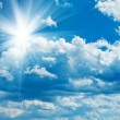 Blue cloudy sky with sun - Stock Photo
