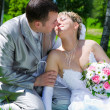 Stock Photo: The wedding pair sits on a grass kiss