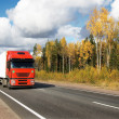 Red truck on autumn highway — Stock Photo