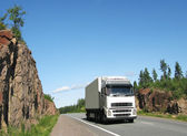 White truck on rocky highway — Stock Photo