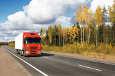 Red truck on autumn highway — Стоковое фото
