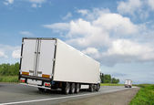 White trucks on country highway — Stock Photo
