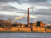 Old factory on river bank — Stock Photo