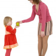 Women give apple to the girl — Stockfoto