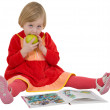 Little girl with book and apple — Stock Photo