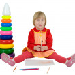 Little girl and toy pyramid and crayons — Stock Photo