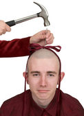 To the young man hammer a bow to a head — Stock Photo