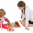 Girl teaching little girl play chess — Stock Photo #1021233