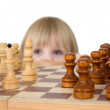 Royalty-Free Stock Photo: Little girl looking chess
