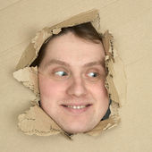 Male face look up from hole in carton — Stock Photo