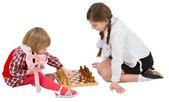 Girl teaching little girl play chess — Stock Photo