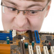 Royalty-Free Stock Photo: Guy bites an old circuit board