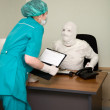 Stock Photo: Patient similar to a mummy and the docto